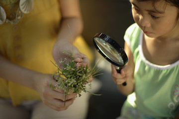 Woman holding plant while young girl looks through magnifying glass
