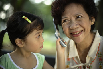 Young girl holding phone to woman's ear