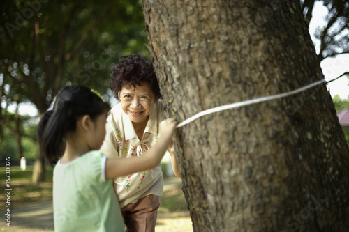 Woman and young girl tying measuring tape around tree trunk