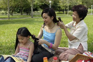 Three generations of women in park braiding each other's hair