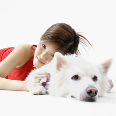 Girl lying with dog indoors