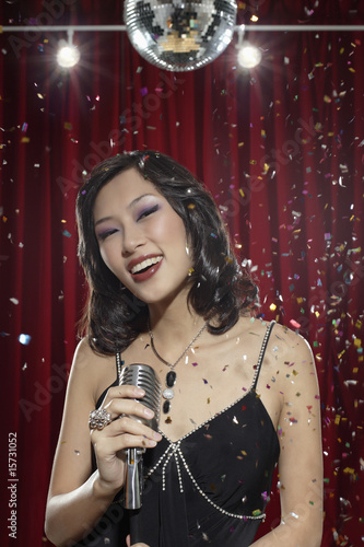 Woman with microphone under disco ball