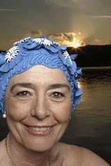 Woman wearing bathing cap by lake