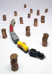 Modello di treno merci con monete su sfondo bianco