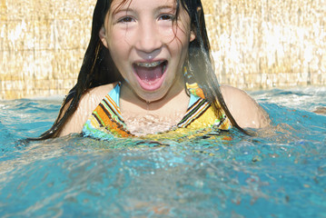 Girl in swimming pool with mouth open