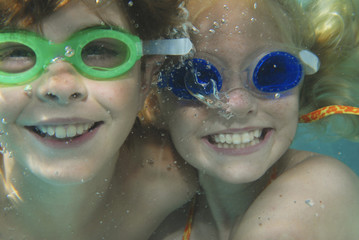 Young boy and girl wearing swim goggles underwater