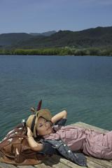 Woman lying on dock with large bag