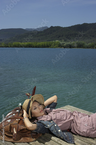 Woman lying on dock with large bag