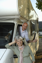 Woman leaning against recreational vehicle with man inside