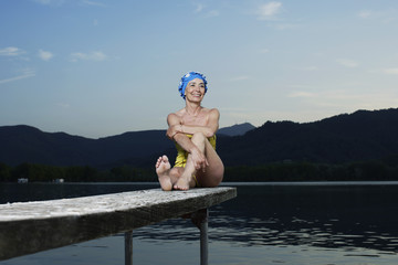 Woman sitting on wooden plank over lake