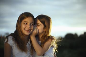 Girl whispering in other girl's ear