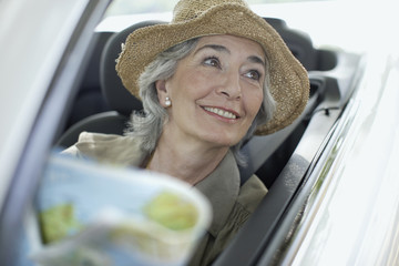 Woman wearing hat smiling and driving a convertible car