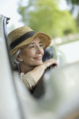 Woman wearing hat smiling in a convertible car