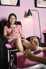 Woman getting a pedicure looking at her mobile phone