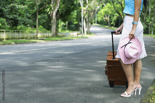 Woman standing with suitcase on side of road
