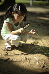 Girl with magnifying glass outdoors