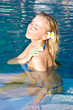 Blonde girl relaxing in water in the pool