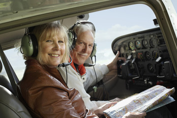 Couple in an airplane cockpit with a map