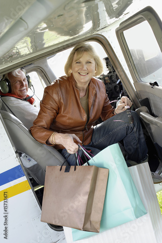 Woman getting out of airplane with shopping bags