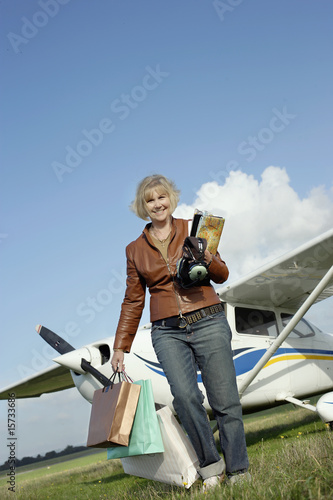Woman walking away from plane with shopping bags