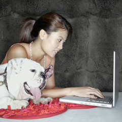 Woman with dog and laptop indoors