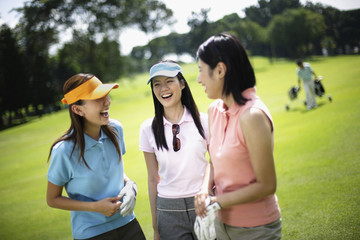 Three women playing golf with man in background