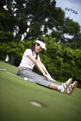Woman sitting on golf course