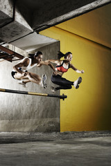 Two athletes jumping a parking garage barrier