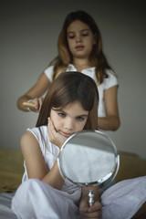 Girl doing another girl's hair