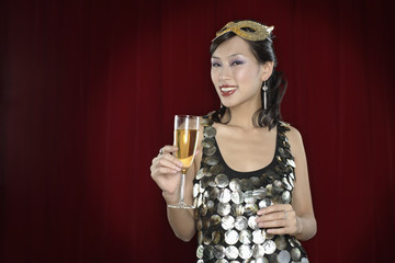 Woman with mask holding glass of champagne