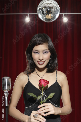 Woman holding rose by microphone
