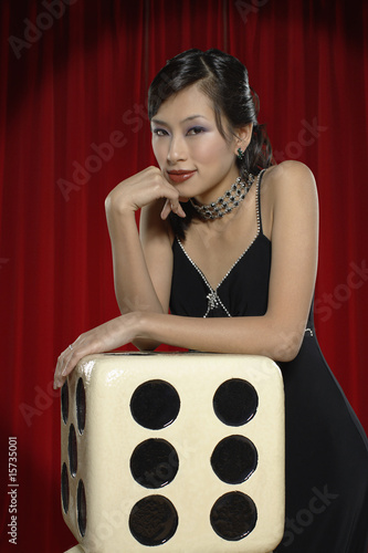 Woman leaning on large dice