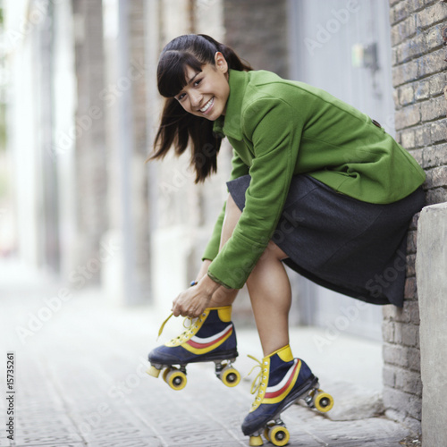 Woman putting on roller skates outdoors