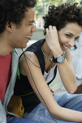 Couple outdoors sharing earbuds