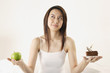Woman deciding on piece of cake or apple