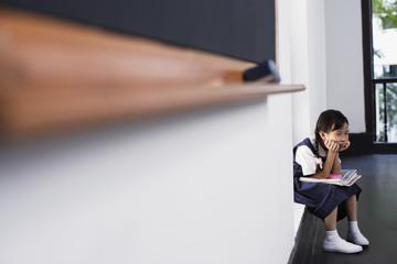 Girl sitting by blackboard in classroom