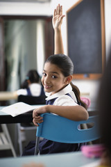 Girl with hand up in classroom with students in background