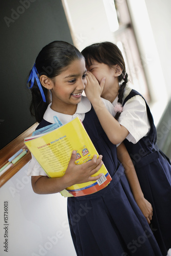 Two girls whispering in classroom