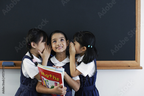 Three girls in classroom whispering