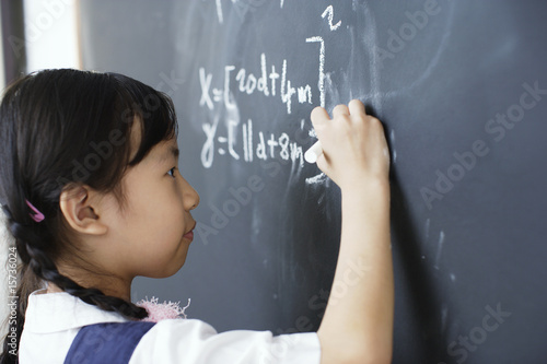 Girl writing on blackboard in classroom