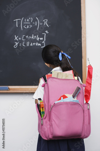 Girl looking at blackboard in classroom