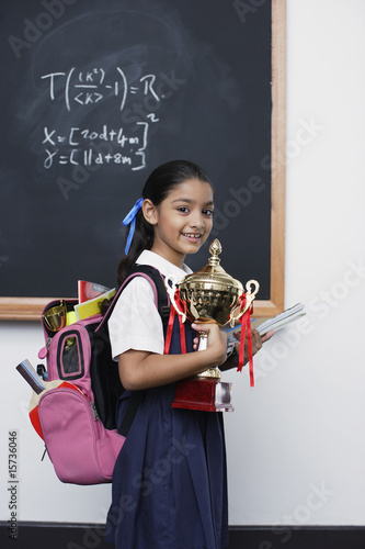 Girl with trophy by blackboard in classroom