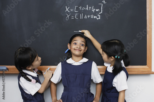 Two girls marking height of other girl on blackboard