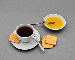 Tea cup, honey and crackers