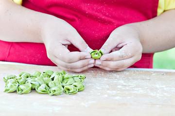 Hands preparing Italian stuffed pasta.