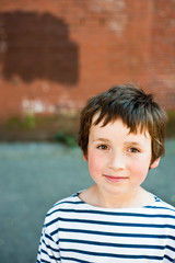 young boy with brick wall behind