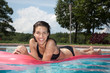 Hispanic woman in black bikini with green eyes on pool float
