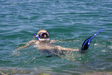 man in the water with fins mask and snorkel