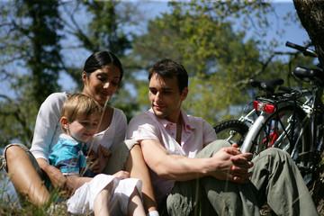 homme et femme avec enfants assis dans l'herbe