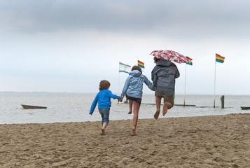 Drtei Kinder mit Regenschim am Strand, Nordsee, Deutschland|